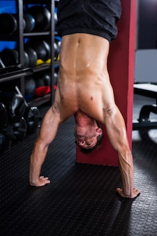 Shirtless atleet doet handstand