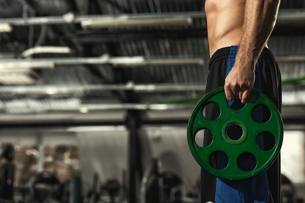 Shirtless atletische man met strak lichaam en six-pack abs met halter gewicht plaat