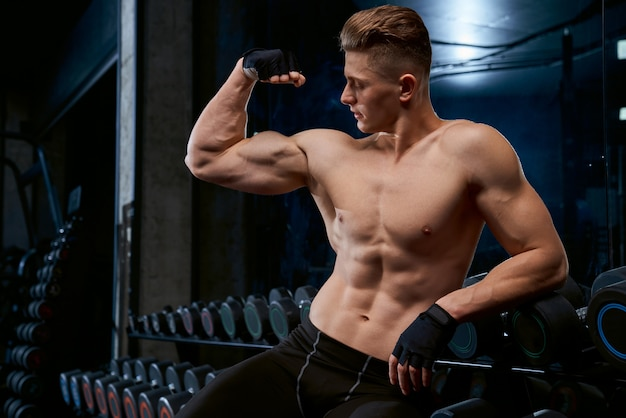 Shirtless bodybuilder poseren in de sportschool.