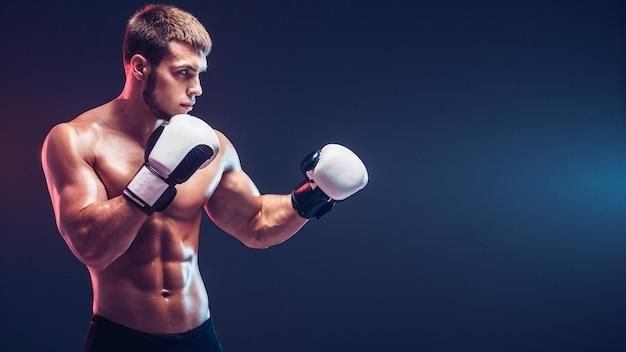 Shirtless bokser met handschoenen op donkere achtergrond. isoleren
