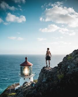 Shirtless fit man staande op een rotsachtige klif in de buurt van een vuurtoren baken en de zee