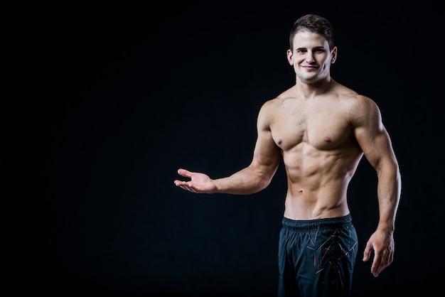 Shirtless gespierde atletische man wijzen met een hand naar lege copyspace. sexy bodybuilder die zijn lichaam toont