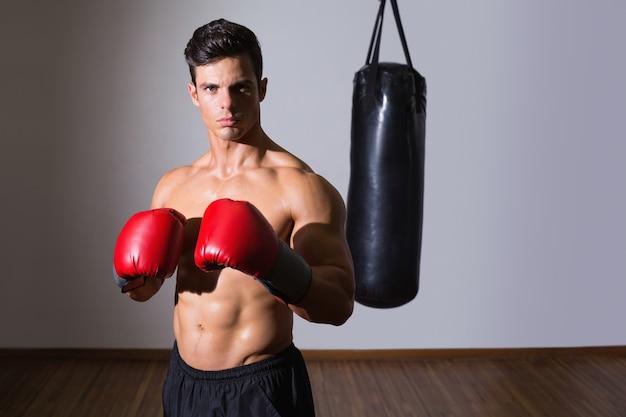 Shirtless gespierde bokser met bokszak in de sportschool