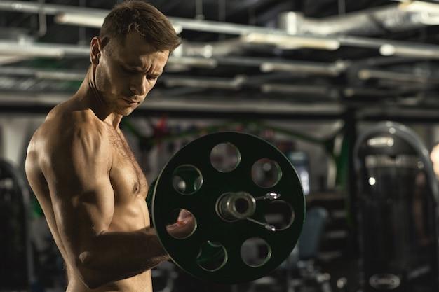 Shirtless gespierde man met sexy fit en strak lichaam doen biceps oefenen met behulp van barbell in de sportschool