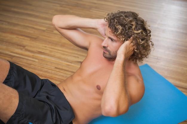 Shirtless jonge man doet push ups in de sportschool