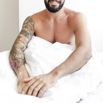 Shirtless jonge man zittend op bed
