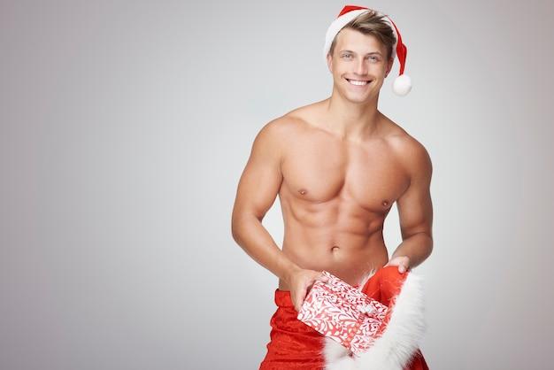 Shirtless man die wat kerstcadeautjes invoegt