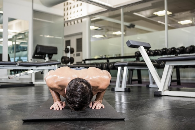 Shirtless man doen push-up in de sportschool