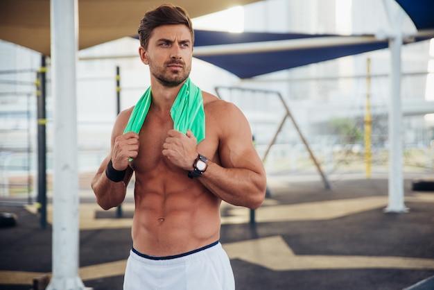 Shirtless man doen trainen en verschillende oefeningen buiten