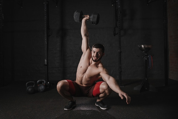Shirtless man doet halter squats en glimlachen. knappe crossfit-atleet die functionele training doet.