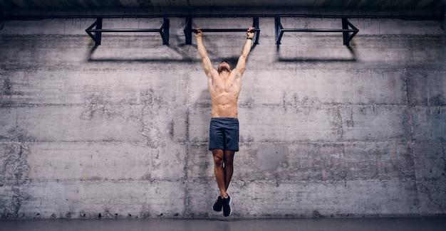 Shirtless man doet pull-ups in de sportschool.
