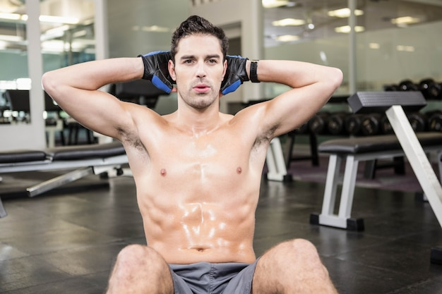 Shirtless man doet zitten in de sportschool