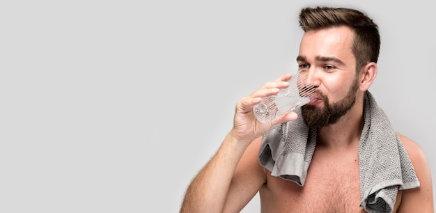 Shirtless man drinkwater met kopie ruimte