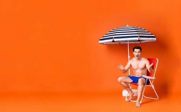 Shirtless man in armen verhoogd geschokt gebaar zittend op een strandstoel