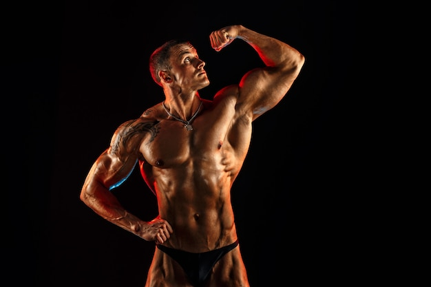 Shirtless man met gespierd topless lichaam arm omhoog te houden.
