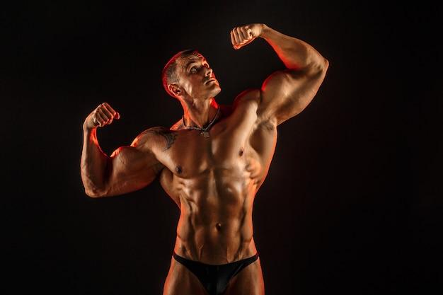 Shirtless man met gespierd topless lichaam armen omhoog te houden.