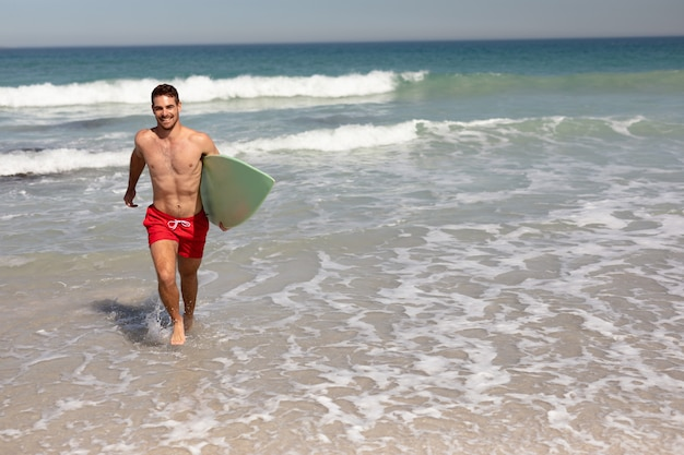 Shirtless man met surfplank lopen op strand in de zon