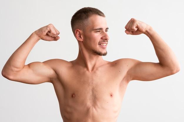 Shirtless man pronken met zijn biceps