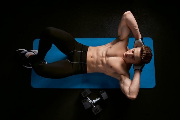 Shirtless man training abs op mat.