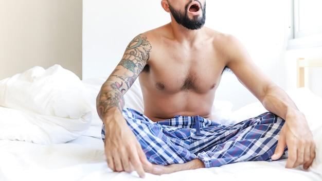 Shirtless man zittend op bed