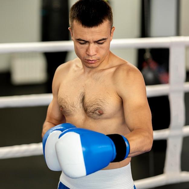 Shirtless mannelijke bokser met beschermende handschoenen