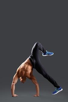Shirtless mannelijke breakdancer die sommige bewegingen op grijze copyspace toont