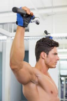 Shirtless mannelijke lichaamsbouwer die trekkracht ups doen bij de gymnastiek