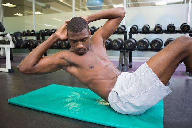 Shirtless mens die buikkraken in gymnastiek doen