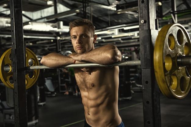 Shirtless sportman die aan de camera kijken die op barbell leunen die na zijn training bij de gymnastiek rusten