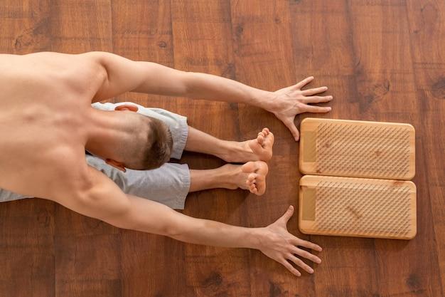 Shirtless sportman zittend op de vloer door yoga therapie pads met metalen haren en voorover buigen met zijn armen en benen gestrekt