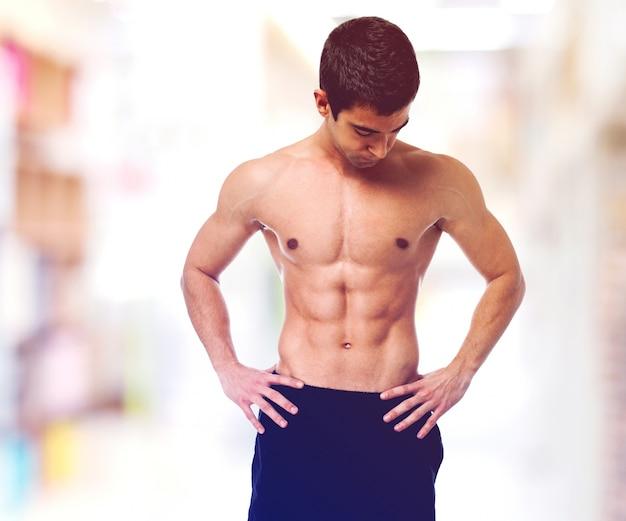 Shirtless tiener toont zijn lichaam
