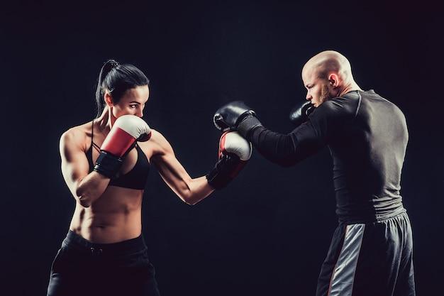 Shirtless vrouw die met trainer bij het in dozen doen en zelfverdedigingsles uitoefenen, studio, donkere achtergrond. vrouwelijke en mannelijke strijd.