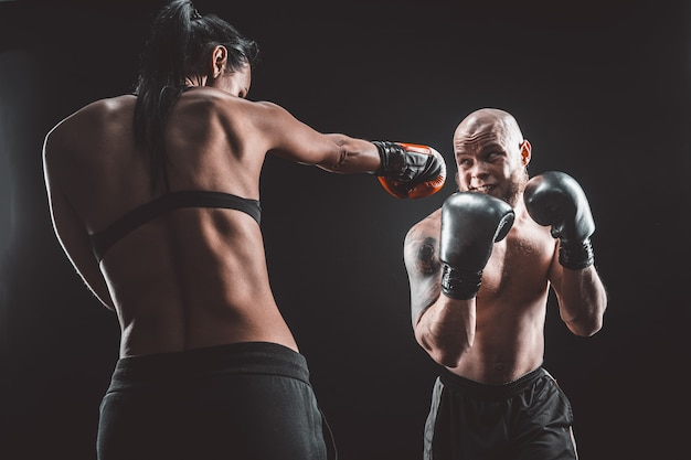 Shirtless vrouw oefenen met trainer op boksen en zelfverdediging les vrouwelijke en mannelijke strijd