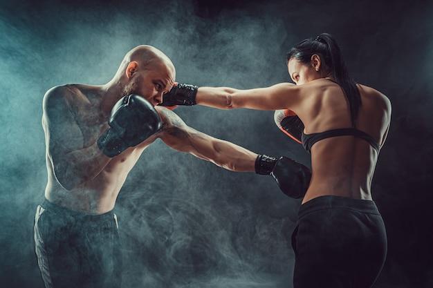 Shirtless vrouw trainen met trainer bij boksen en zelfverdediging les, studio, donkere ruimte