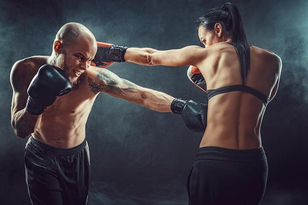 Shirtless vrouw trainen met trainer bij boksen