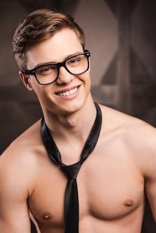 Shirtloos bedrijf. knappe jongeman in brillen en stropdas die naar de camera kijkt en glimlacht terwijl hij tegen een metalen achtergrond staat