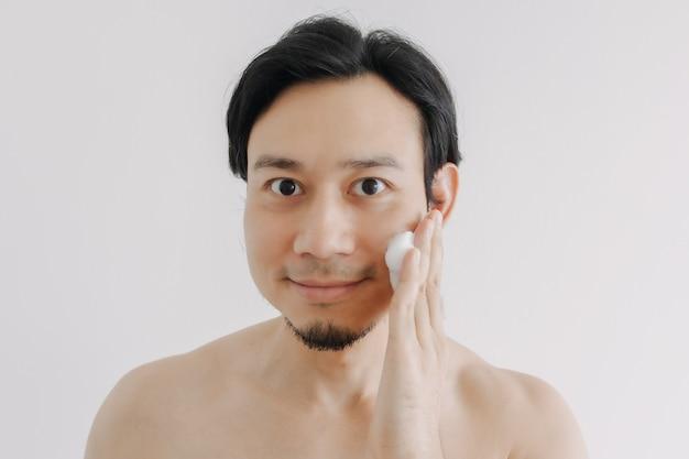 Shirtloze man pronkt met zijn gezicht en huid voor huidverzorgingsproduct
