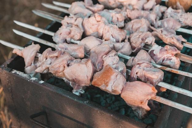 Shish kebab gebakken bij de grill. varkensvlees shish kebab op vleespengrill wordt gebraden in het park dat