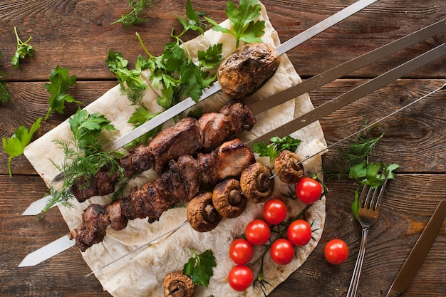 Shish-kebab met veldchampignons en kerstomaatjes op lavash.