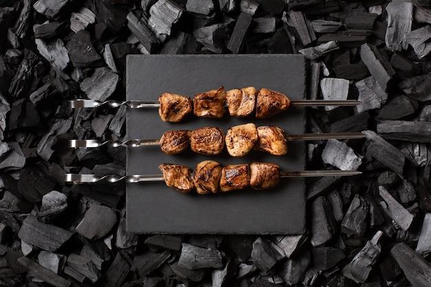 Shish kebab op spiesjes. drie porties van gegrild vlees op een stenen plaat.