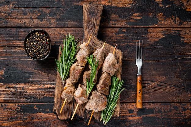 Shish kebab op spiesjes met kruiden op een houten bord. donkere houten tafel. bovenaanzicht.