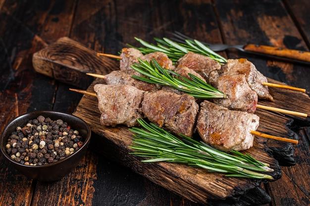 Shish kebab op spiesjes met kruiden op een houten bord