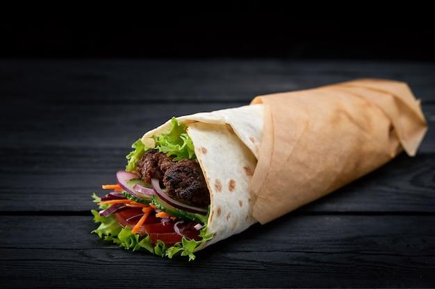 Shoarma gerold in lavash, vochtig gegrild vlees met ui, kruiden en groenten op houten zwarte achtergrond.