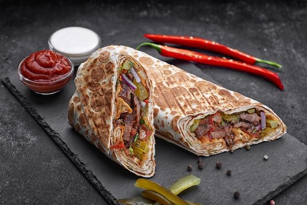Shoarma met kalfsvlees, met saus, uien, augurken, kruiden en hete rode peper, op leisteen, tegen een donkere betonnen ondergrond