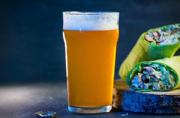 Shoarma met kip, groenten en zoete saus, een glas licht ongefilterd bier