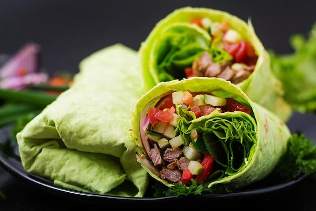 Shoarma van sappig rundvlees, sla, tomaten, komkommers, paprika en ui in pitabroodje met spinazie. dieet menu