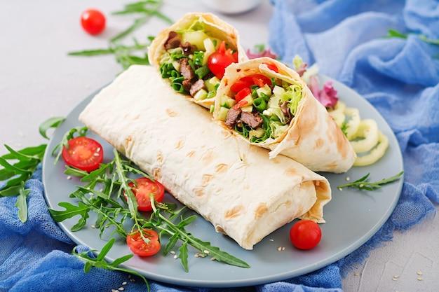 Shoarma van sappig rundvlees, sla, tomaten, komkommers, paprika en ui in pitabroodje.