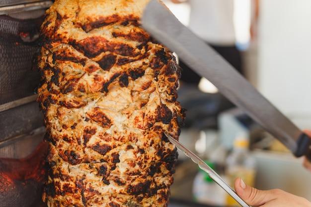 Shoarma vlees wordt gesneden