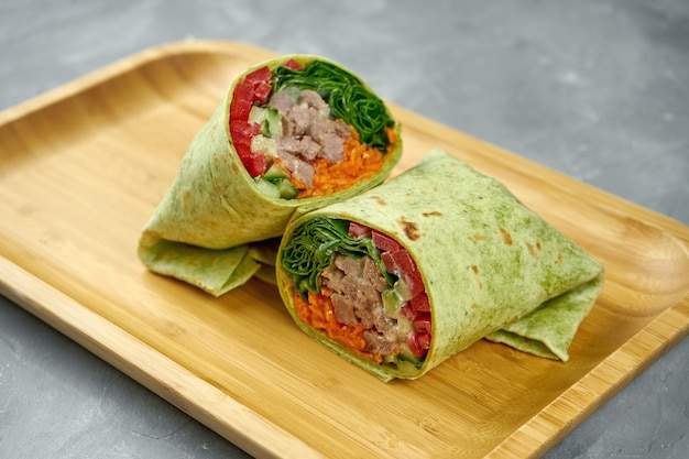 Shoarmabroodje met rundvlees, paprika, wortelen en slablaadjes in groen pitabroodje op een houten bord op een grijze tafel. close-up, selectieve aandacht