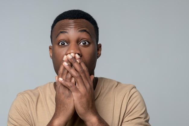 Shock, emotie. jonge geschokt donkere man met grote ogen aanraken van de handpalmen naar de mond op een grijze achtergrond